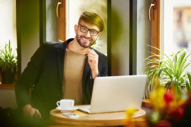Homme émotionnel souriant à l'ordinateur portable