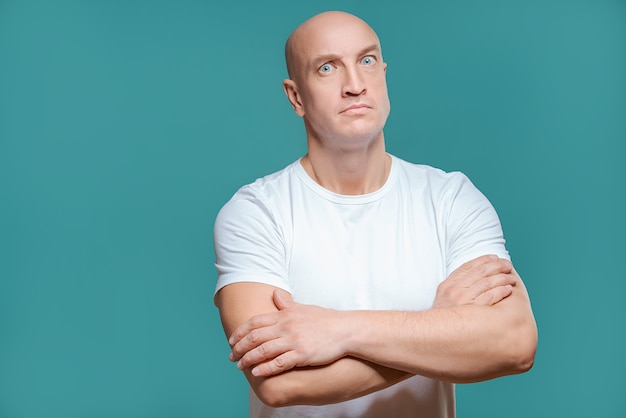 Homme émotionnel en t-shirt blanc avec une expression faciale en colère sur fond