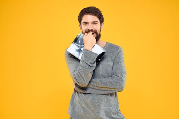 Homme émotionnel avec tablette en mains technologie internet mode de vie fond jaune. photo de haute qualité