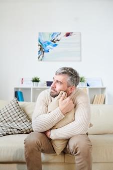 Homme émotionnellement instable embrassant un coussin dans la salle des psychiatres