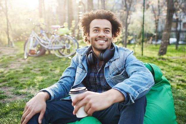 Homme émotive à la peau sombre avec une coiffure afro, assis sur une chaise dans le parc tout en parlant à quelqu'un et en buvant du café, souriant largement et exprimant des émotions positives.
