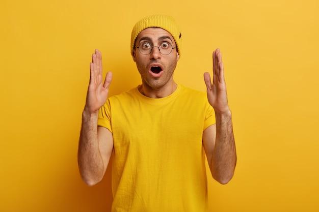 Un homme ému étourdi étend les mains et montre quelque chose d'énorme, démontre une grande grande taille, parle de quantité, a une expression choquée