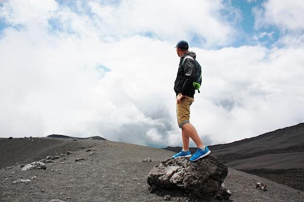 L'homme encouragé sur la colline regarde l'éruption du volcan etna. etna, italie.