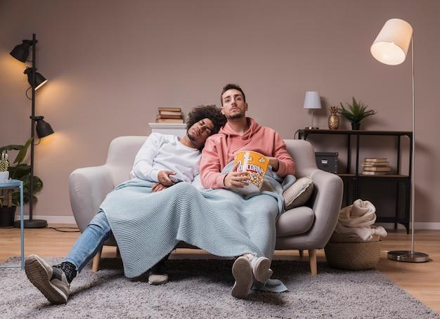 Homme endormi sur un ami tout en regardant la télévision
