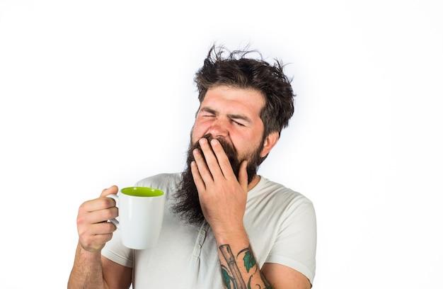 Un homme endormi ayant une tasse de café dans la cuisine, un homme barbu béant tient une tasse de thé, des rafraîchissements et de l'énergie