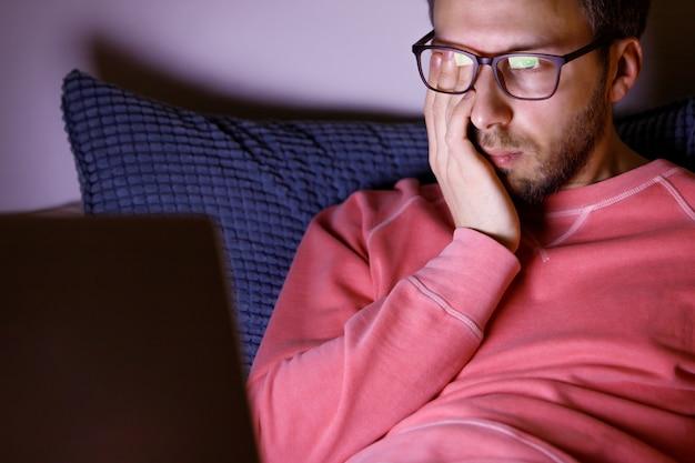 Homme endormi dans des verres en se frottant les yeux, se sent fatigué après avoir travaillé sur un ordinateur portable