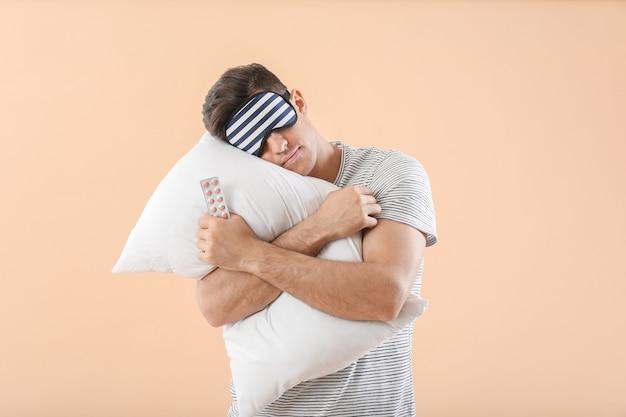 Homme endormi avec des pilules et un oreiller sur fond de couleur