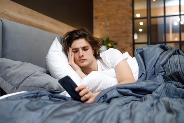 Homme endormi se réveillant tôt après avoir entendu le signal du réveil le lundi matin