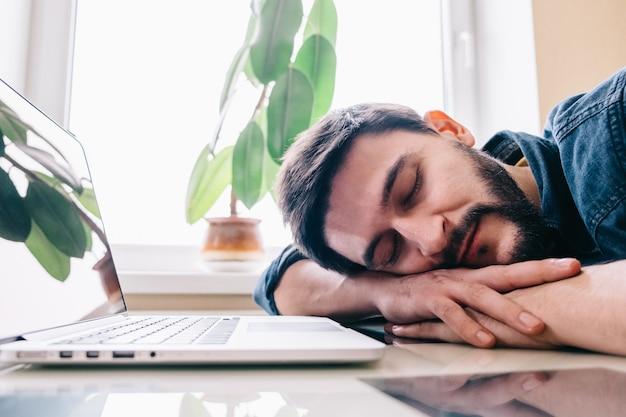Homme endormi avec son ordinateur portable