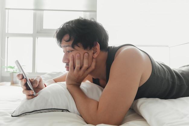 Un homme endormi utilise un smartphone en position couchée sur le lit.