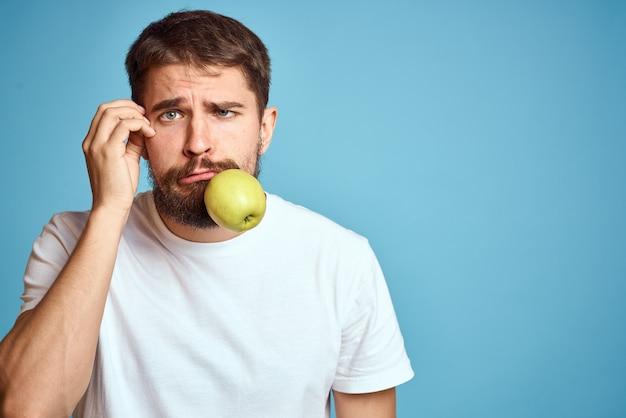 Un homme énergique avec une pomme verte sur un fond bleu fait des gestes avec ses mains copiez les émotions de l'espace. photo de haute qualité