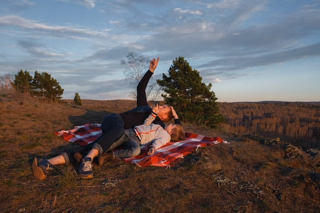 Un homme avec un enfant allongé sur une couverture rouge dans les montagnes et regarde le ciel.