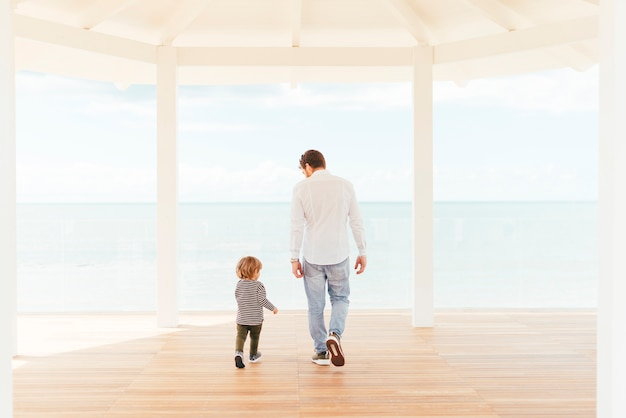 Homme et enfant en bas âge marchant sur le porche