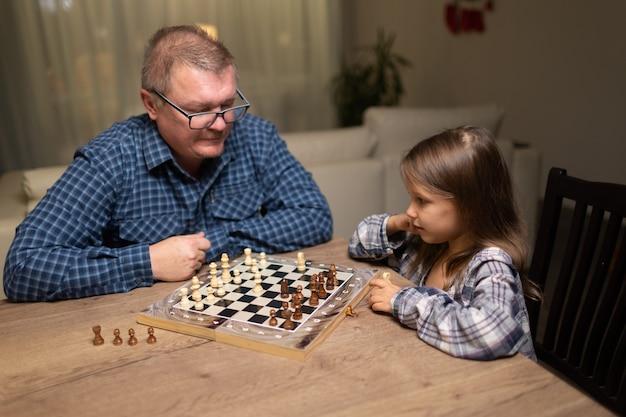 Un homme et un enfant jouent aux échecs, papa apprend à sa fille à jouer aux échecs.
