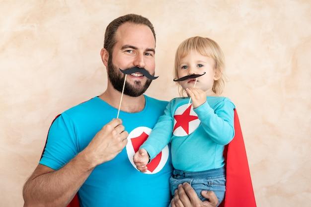 Homme et enfant super héros à la maison. père et fils de super-héros s'amusant ensemble.