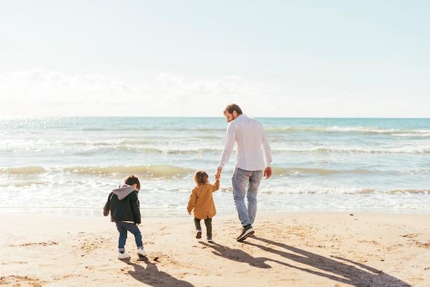 Homme avec des enfants en bas âge marchant vers la mer