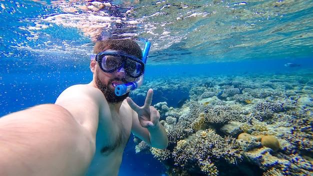 Un homme engagé dans la plongée en apnée a plongé au fond de la mer rouge et se prend en photo sur fond de coraux