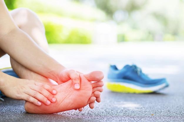 L'homme enlève les chaussures touchant le pied douloureux de la cheville tordu ou cassé.