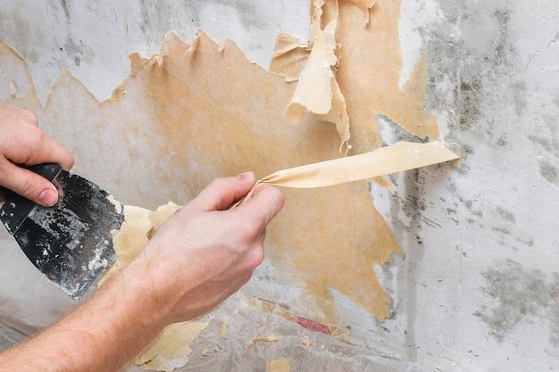 Un homme enlève le vieux papier peint avec une spatule et un vaporisateur avec de l'eau.