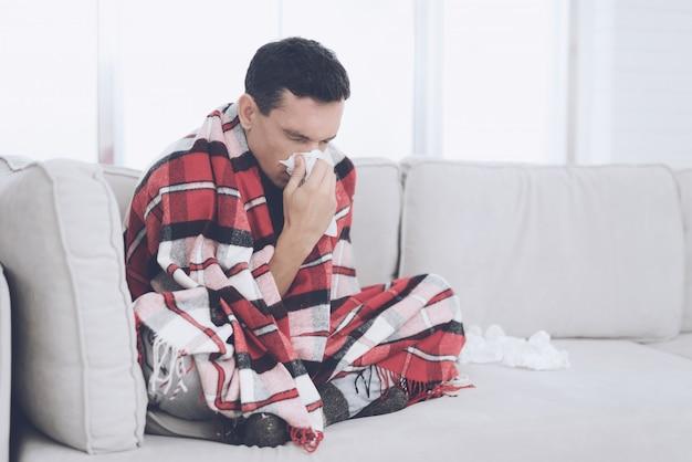 Un homme enrhumé est assis sur le canapé et se cache derrière un tapis rouge.