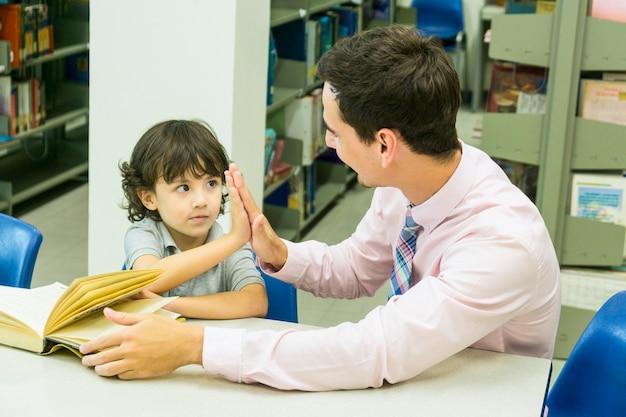 Homme enseignant et élève kid apprendre avec livre sur fond d'étagère