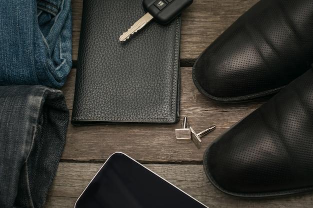 Homme ensemble pour la journée de clé de portefeuille, jeans, smartphone et voiture sur planche de bois.