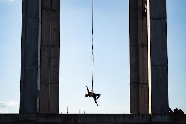 L'homme entourant les colonnes de cri faisant des exercices de gymnastique en plein air sur fond de ciel bleu