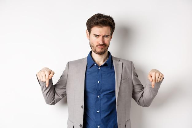 Homme entrepreneur barbu déçu fronçant les sourcils et pointant vers le bas avec une émotion négative