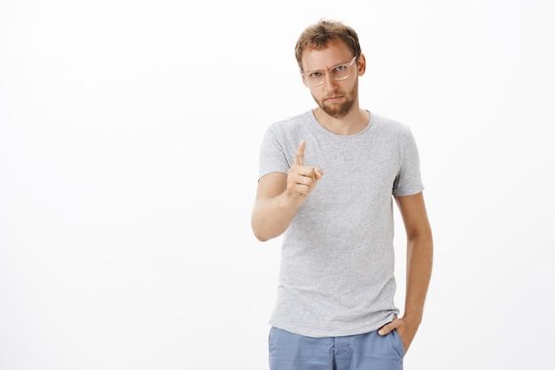 Homme entrepreneur ciblé donnant des instructions sur le devoir étant strict et sérieux avec des employés secouant l'index, pointant, insatisfait ou déçu du mauvais travail sur un mur blanc