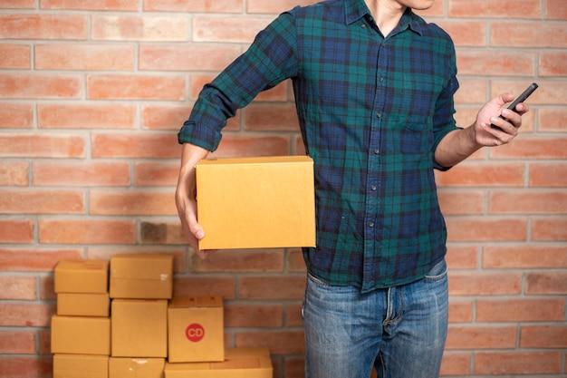 Un homme entrepreneur propriétaire une pme est une boîte d'emballage pour envoyer son client