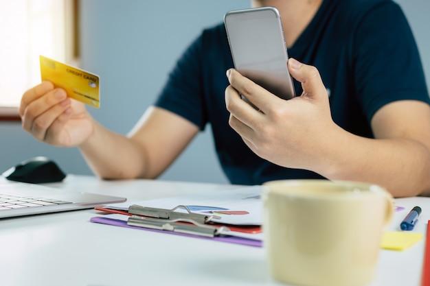 Homme, entrer, code sécurité, à, téléphone portable, et, payer, par, carte de crédit, et, document, rapport, bureau