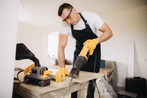 Homme d'entretien à l'aide d'une scie électrique pour réparer les meubles