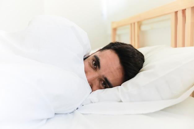 Homme enveloppé dans une couverture allongée sur le lit