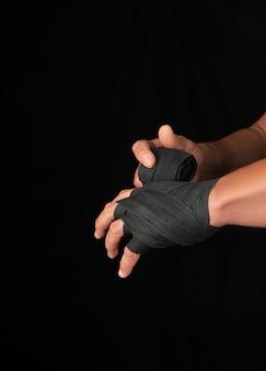 Un homme enveloppe ses mains dans un bandage textile noir pour le sport