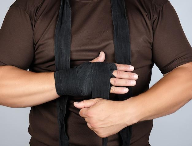 L'homme enveloppe ses mains dans un bandage textile noir