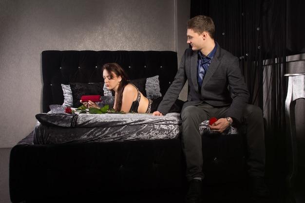 Un homme envisage de proposer à sa petite amie assise au bout du lit avec la boîte à bagues à la main, rassemblant son courage