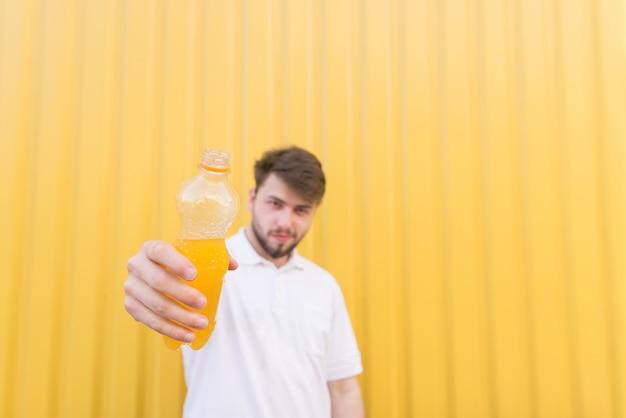 Un homme envoie une bouteille de sa main. un homme offre une bouteille de boisson à l'orange.