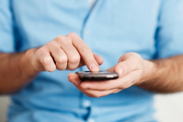 Homme envoyant des sms sur téléphone mobile