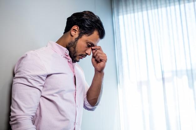 Homme épuisé, debout contre le mur et regardant vers le bas