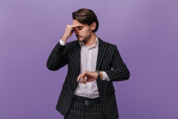 Homme épuisé occupé aux cheveux noirs, chemise claire et costume rayé pensant à quelque chose après avoir regardé la montre