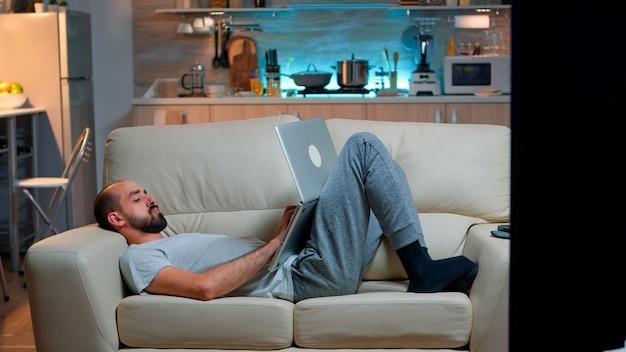Homme épuisé s'endormir tout en travaillant sur un projet de communication internet