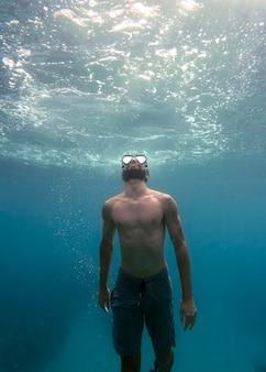 Homme avec équipement de plongée nageant dans l'océan
