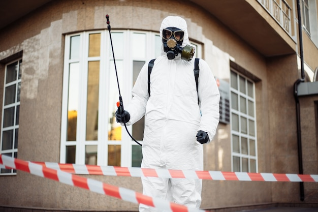 L'homme en équipement de protection désinfectant la ville