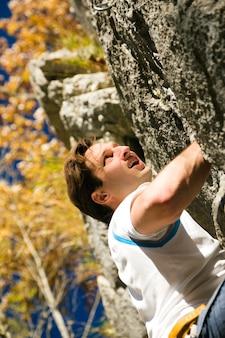 Homme escaladant le rocher