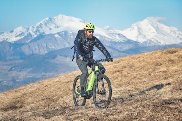 Homme escalade une prairie de montagne avec vélo de montagne