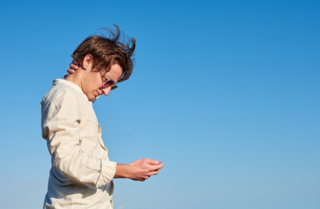 Homme espagnol aux cheveux longs, des lunettes et une chemise beige regardant son téléphone et se grattant la tête sur un ciel bleu clair