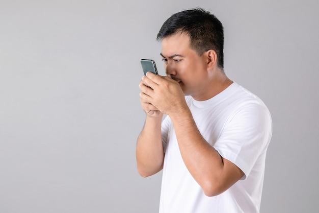 Homme essayant de regarder de plus près le smartphone