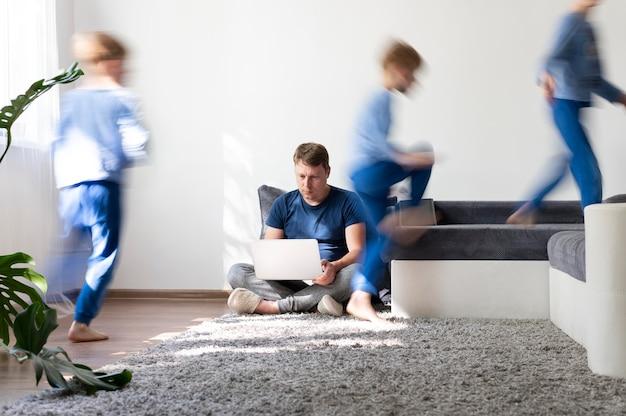 Homme essayant de travailler sur un ordinateur portable à la maison pendant que ses enfants courent partout