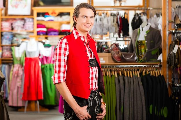 Homme essaye tracht ou lederhosen dans un magasin