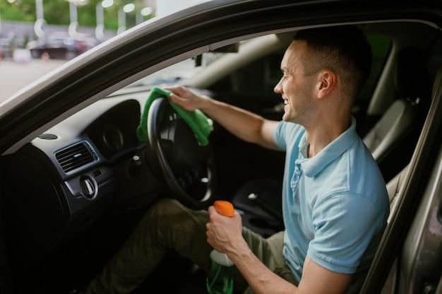L'homme essuie l'intérieur de la voiture avec un chiffon, lavage automatique à la main